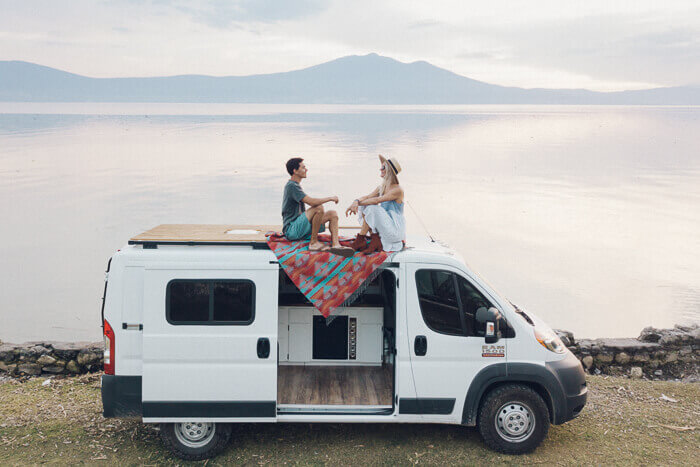 a couple sit on top of a self build campervan in front of the sea