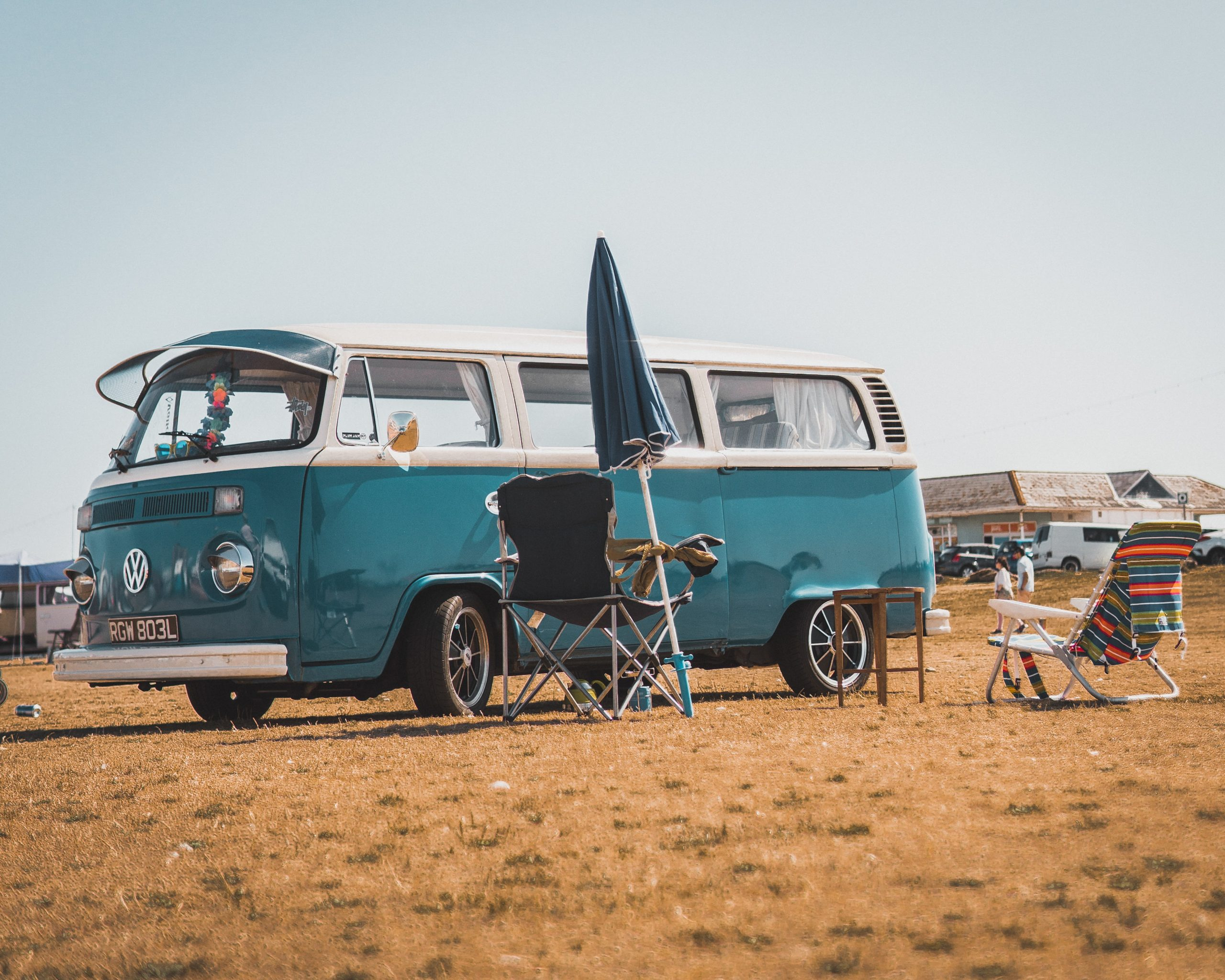 a blue VW camper is parked next to foldable chairs