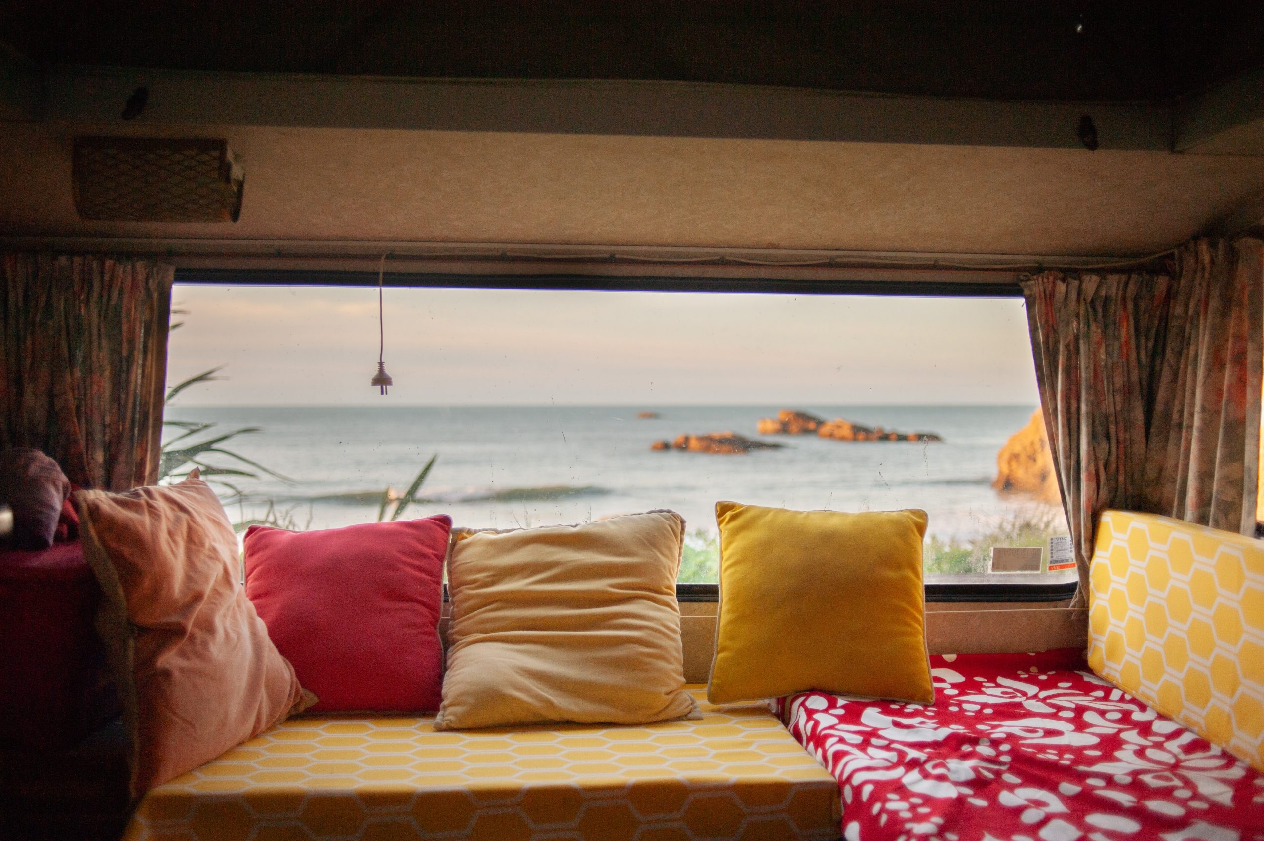 a view from a camper window with brightly coloured cushions