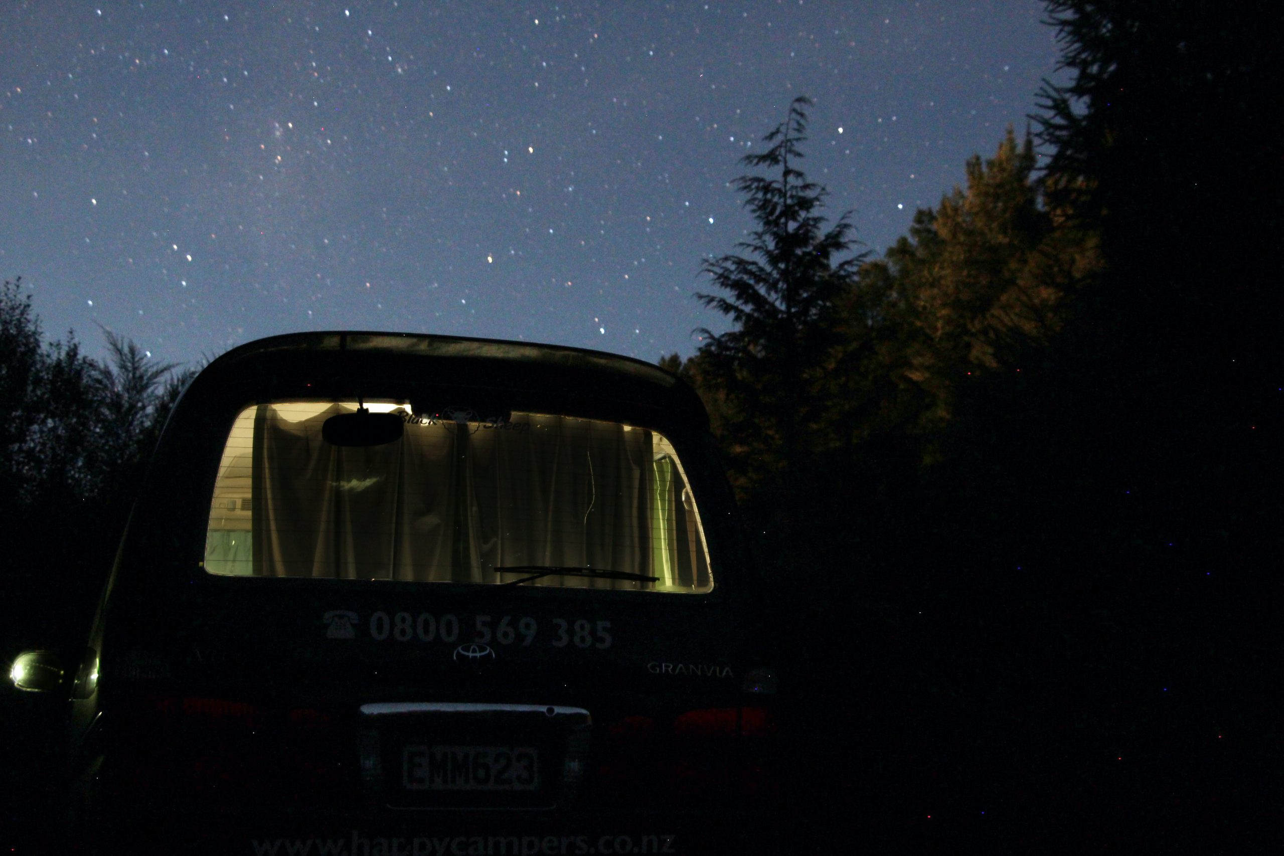 a campervan under the stars with hanging curtains in the window