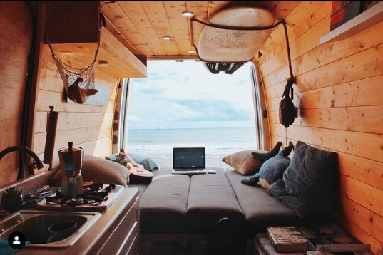 a view out the back of a campervan with a section pop up bed