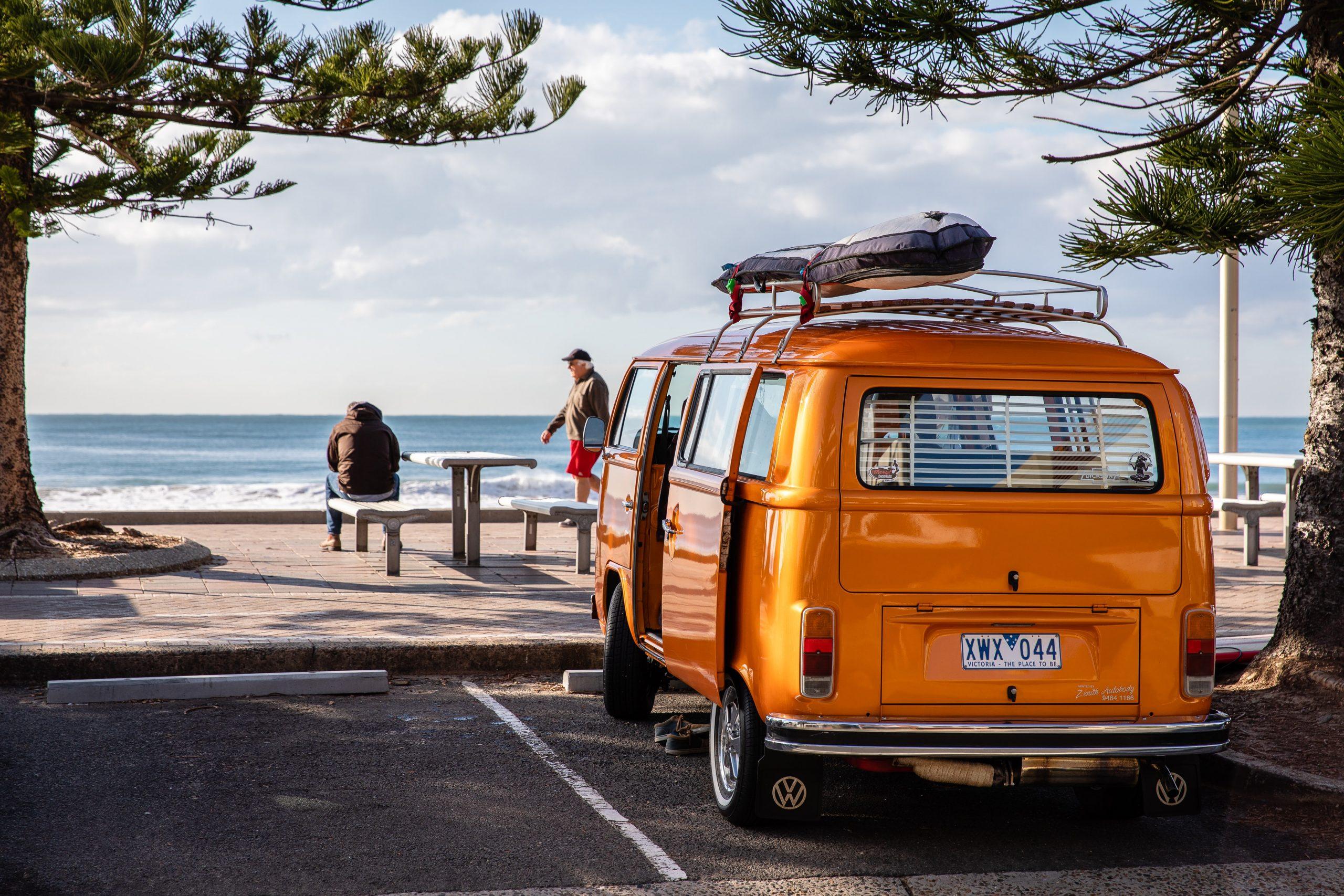 an orange campervan overlooks a beach scene