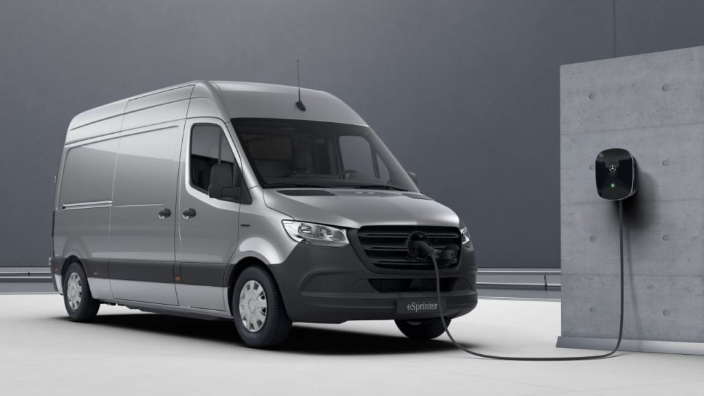 a silver Mercedes eSprinter plugged into an electric charging point