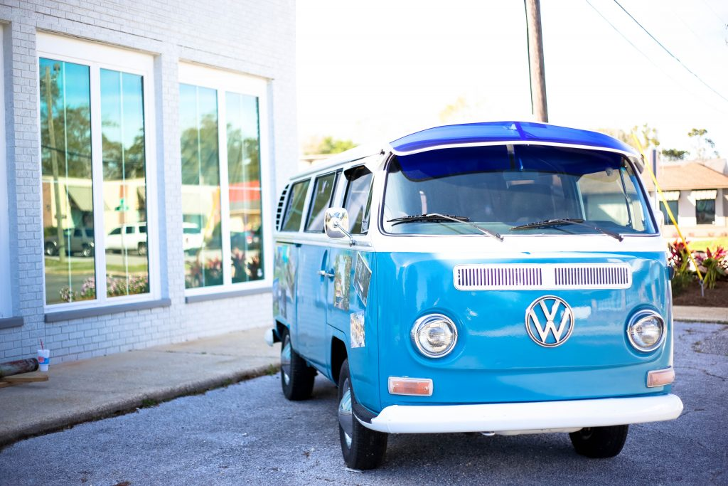a bright blue VW camper parked in the sunshine