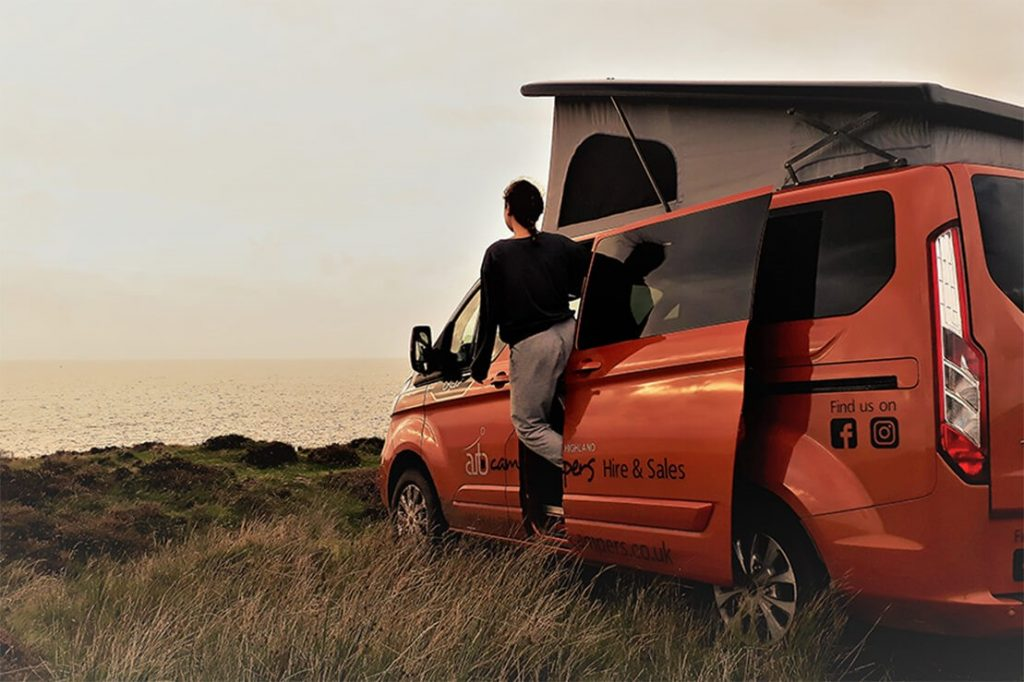 a woman leans out from a small orange campervan