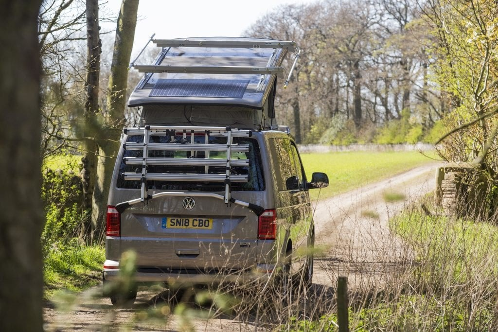 a jerba campervan drives down a quiet track